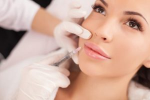 The dentist injects the dermal filler into the patient's skin.