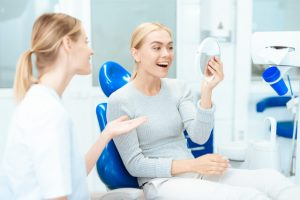 The dentist shows the result of dermal filler to the patient.