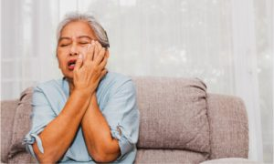 An elderly woman experiencing severe toothache, associated with swelling.